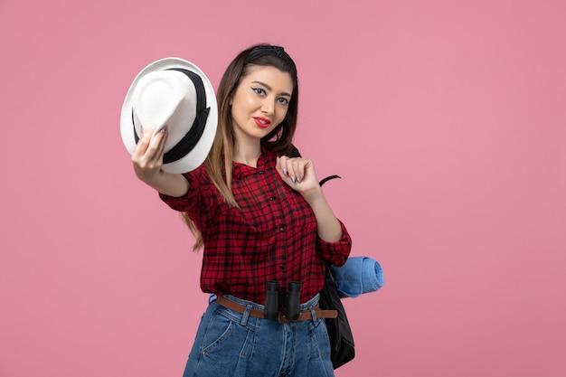 Vista frontale giovane femmina in camicia rossa con cappello su sfondo rosa chiaro donna di colore umano