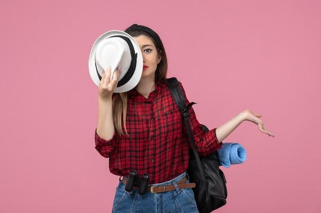 Giovane femmina di vista frontale in camicia rossa con il cappello sul modello umano della donna di colore di sfondo rosa