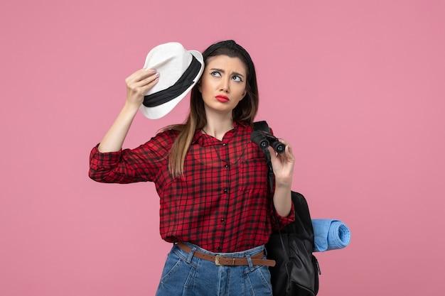 Vista frontale giovane femmina in camicia rossa con cappello su sfondo rosa colore donna umana