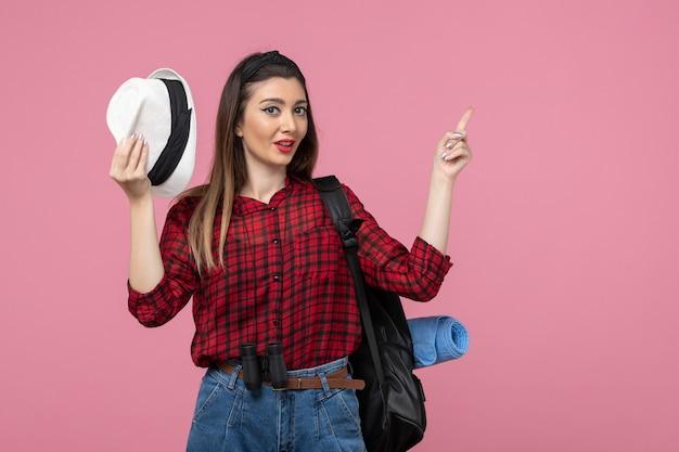 Giovane femmina di vista frontale in camicia rossa con il cappello sul colore della donna umana di sfondo rosa