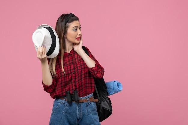 Giovane femmina di vista frontale in camicia rossa con il cappello sui colori della donna umana dello scrittorio rosa