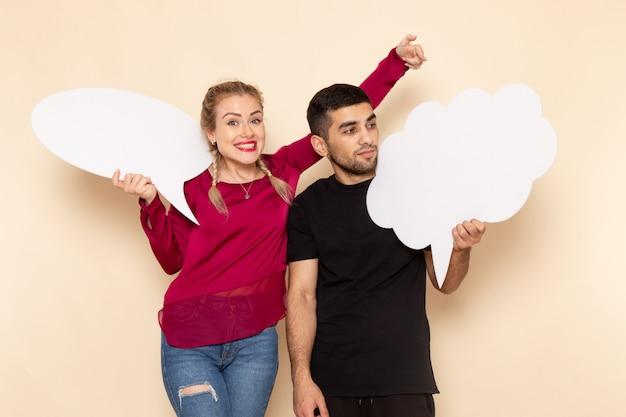Giovane femmina di vista frontale in camicia rossa con i segni bianchi della tenuta del maschio sulla foto del panno femminile dello spazio crema