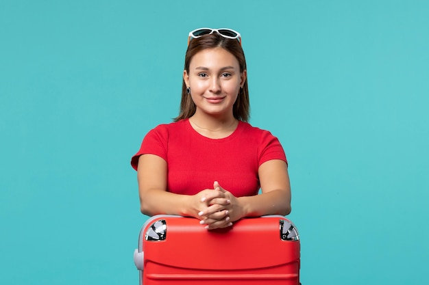 Giovane femmina di vista frontale in camicia rossa con il sacchetto rosso che si prepara per la vacanza sullo spazio blu