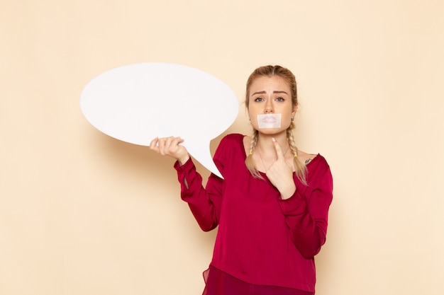 Front view young female in red shirt with tied mouth and holding white sign on the cream space female cloth  photo violence domestic