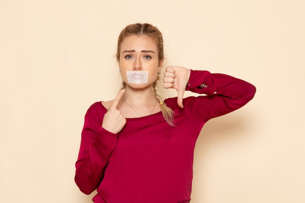 Front view young female in red shirt with tied mouth showing unlike sign on the cream space female cloth  photo violence domestic