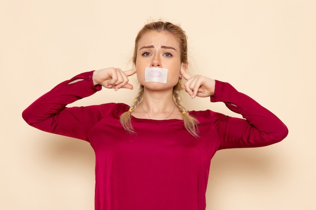 Front view young female in red shirt with tied mouth shutting her ears on the cream space female cloth  photo violence domestic