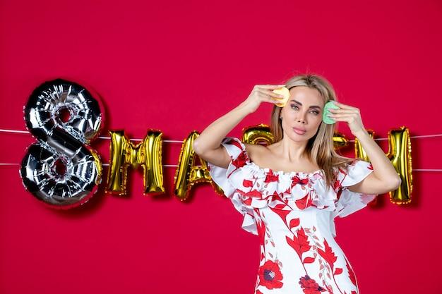 Vista frontale giovane donna che rimuove con spugne su rosso decorato