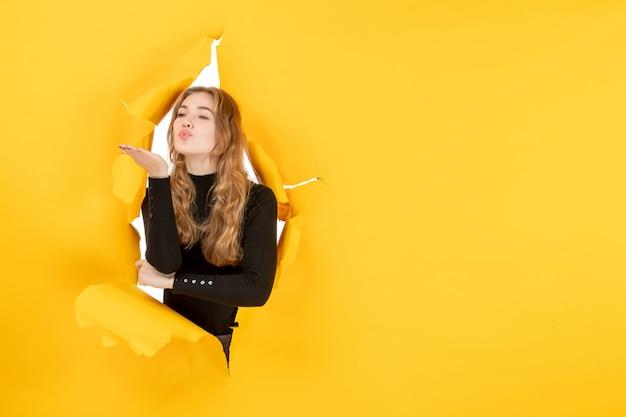 Вид спереди молодая женщина, отправляющая поцелуи на желтой разорванной стене