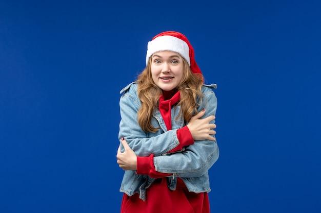 Вид спереди молодой женщины, дрожащей от холода на синем столе, цветная эмоция, рождественский праздник