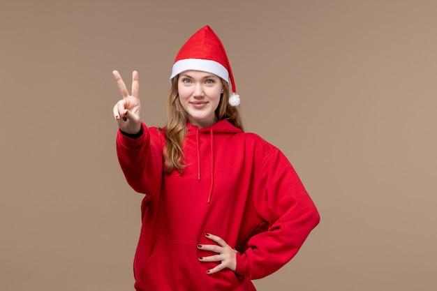 Вид спереди молодая женщина, показывающая номер на коричневом фоне, эмоции, рождественский праздник