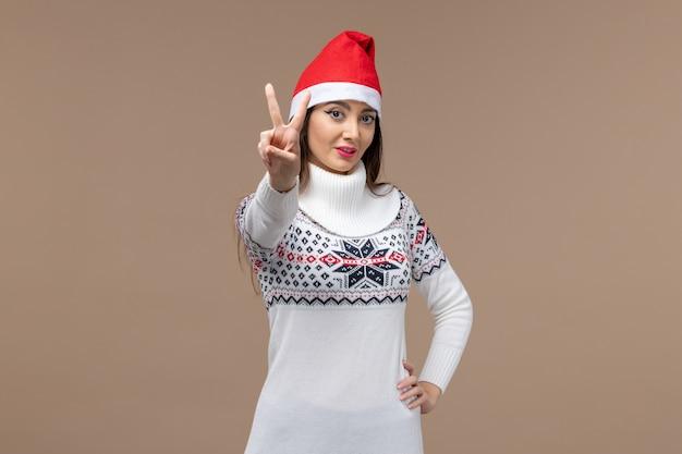 正面図茶色の背景の休日のクリスマスの感情に番号を示す若い女性