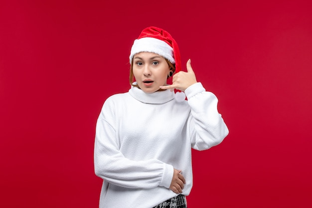 Vista frontale giovane femmina che mostra la telefonata posa su sfondo rosso