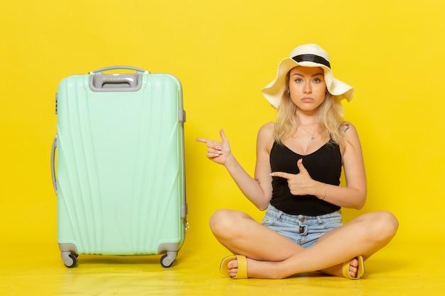 黄色の壁の旅の休暇の太陽の航海の旅の女の子に彼女の緑のバッグと一緒に座っている正面図若い女性