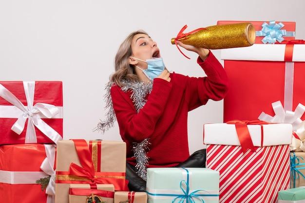 Вид спереди молодая женщина, сидящая вокруг рождества, представляет, пьет шампанское