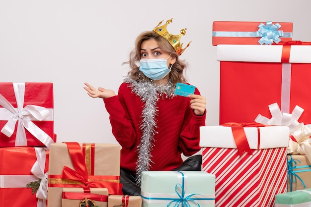 銀行カードを保持しているクリスマスプレゼントの周りに座っている正面図