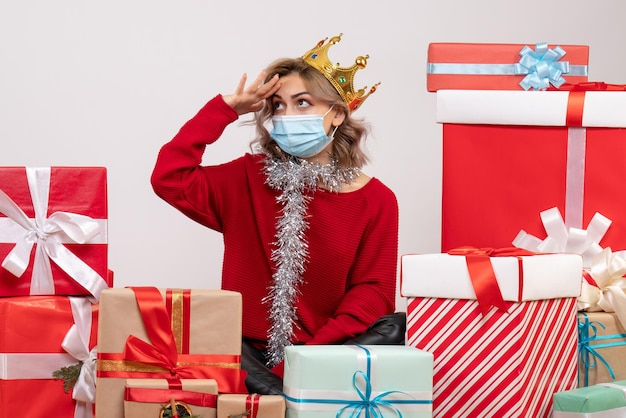 Вид спереди молодая женщина, сидящая вокруг рождественских подарков в маске