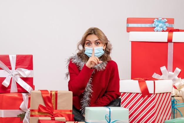マスクでクリスマスプレゼントの周りに座っている正面図若い女性