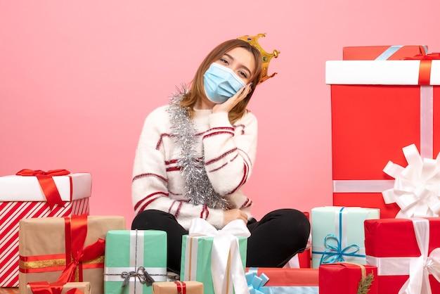 Вид спереди молодая женщина, сидящая вокруг рождественских подарков в стерильной маске