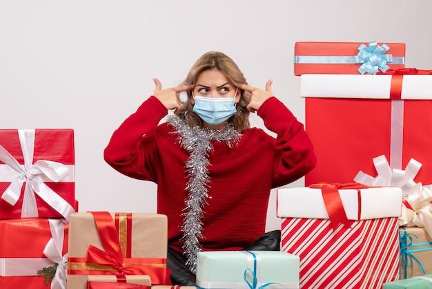 Giovane femmina di vista frontale che si siede intorno ai regali di natale in maschera