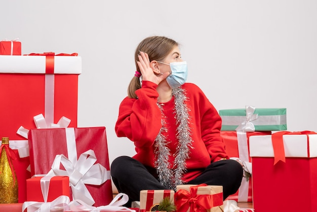 Front view young female sitting around christmas presents in mask
