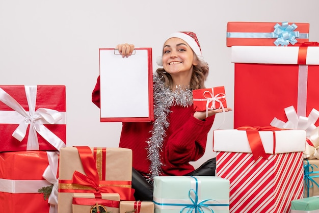Front view young female sitting around christmas presents with note