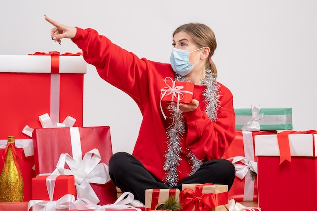 Giovane femmina di vista frontale che si siede intorno ai regali di natale
