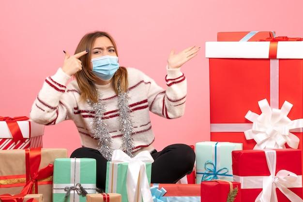Вид спереди молодая женщина сидит вокруг рождественских подарков