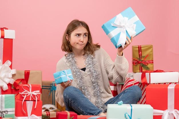 Giovane femmina di vista frontale che si siede intorno ai regali di natale differenti