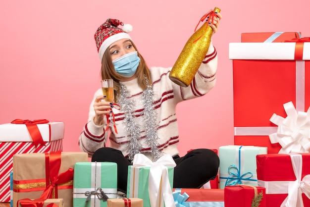 プレゼントの周りに座って祝う正面図若い女性