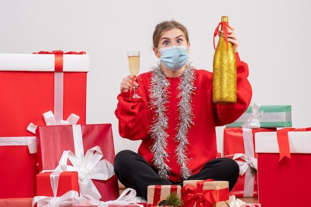 샴페인과 축하 선물 주위에 앉아 전면보기 젊은 여성