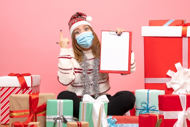 Front view young female sitting around presents with file note