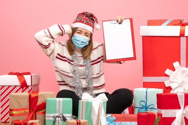 Вид спереди молодая женщина, сидящая вокруг подарков с файловой заметкой