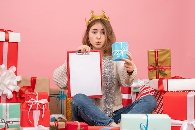 Giovane femmina di vista frontale che si siede intorno ai regali con la nota nelle sue mani