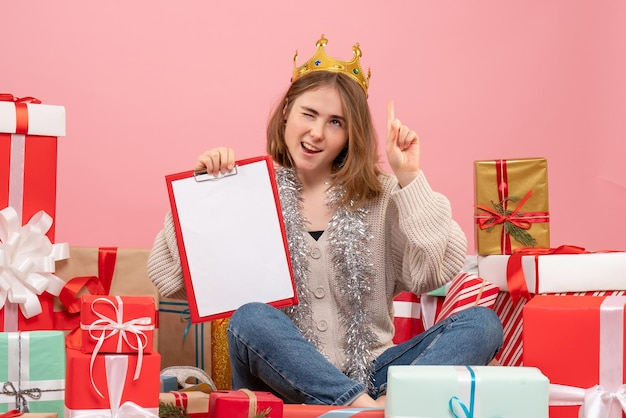 Front view young female sitting around presents with note in her hands