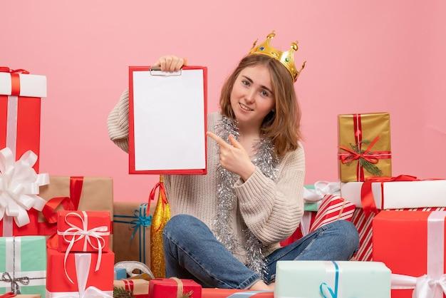 Вид спереди молодая женщина, сидящая вокруг подарков с запиской в руках
