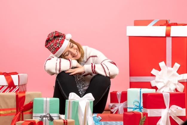 Вид спереди молодая женщина сидит вокруг подарков