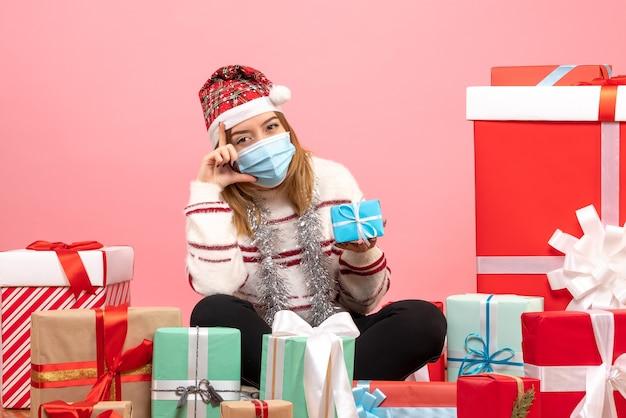 プレゼントの周りに座っている正面図若い女性