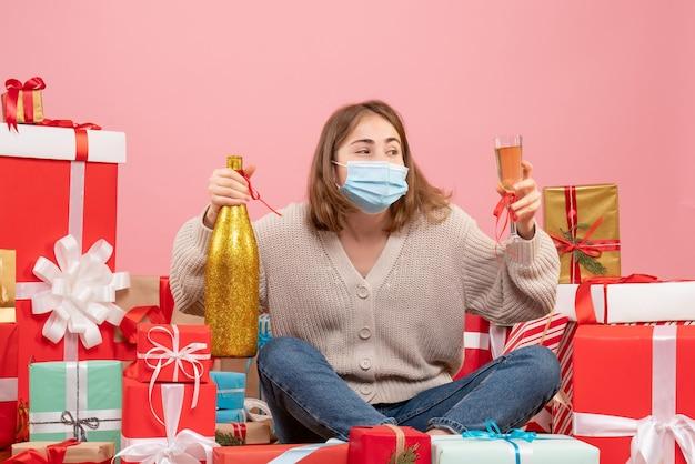 크리스마스 주위에 앉아 전면보기 젊은 여성 샴페인 축하 선물 무료 사진