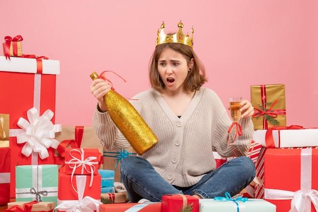 Giovane femmina di vista frontale che si siede intorno ai regali di natale che celebrano con champagne