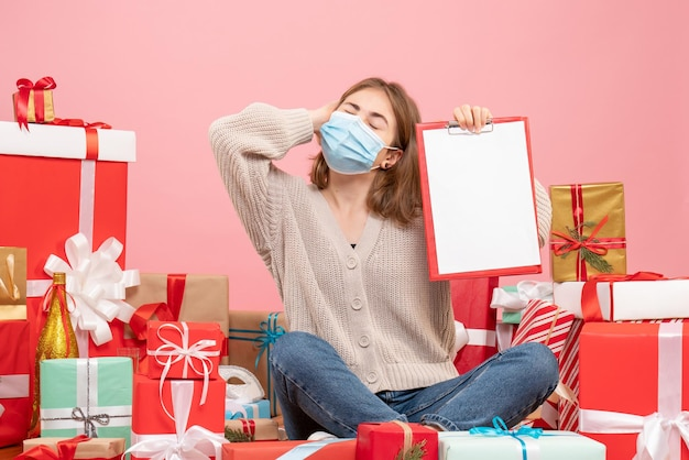クリスマスの周りに座っている正面図の若い女性は、メモとマスクで提示します