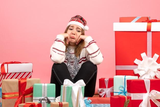 크리스마스 주위에 앉아 전면보기 젊은 여성 슬픈 선물