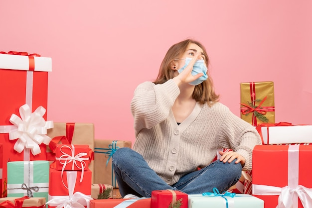 Front view young female sitting around xmas presents in sterile mask