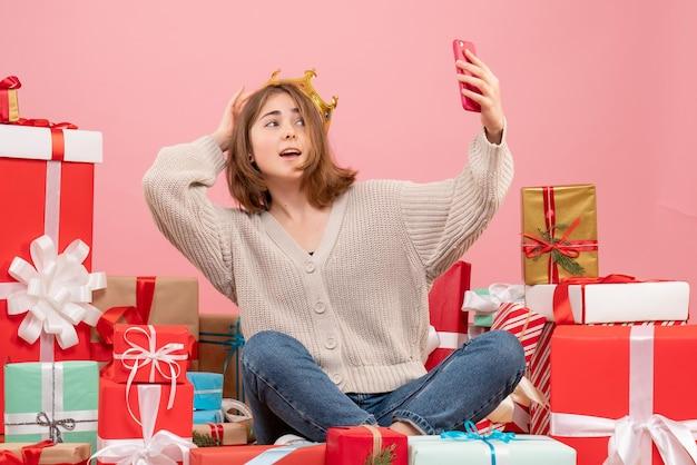 크리스마스 주위에 앉아 전면보기 젊은 여성 선물 복용 selfie