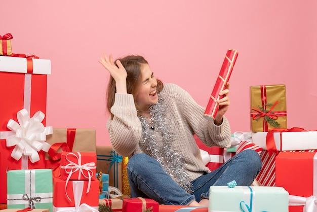 Вид спереди молодая женщина, сидящая вокруг рождественских подарков