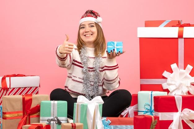 クリスマスプレゼントの周りに座っている正面図若い女性