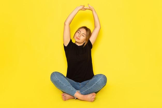 Una giovane femmina di vista frontale che si siede in camicia nera e blue jeans che fanno ginnastica sul colore giallo