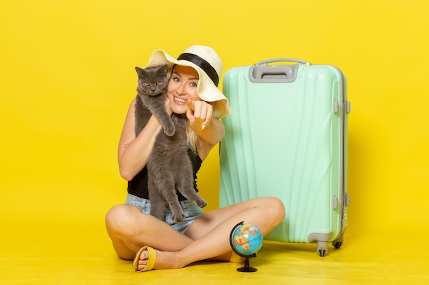 Front view young female sitting and hugging kitten on yellow wall trip vacation voyage sea journey sun