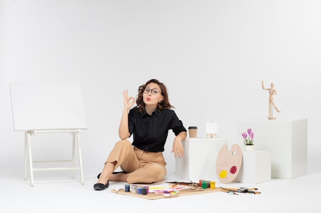 흰색 배경에 이젤과 페인트로 방 안에 앉아 전면보기 젊은 여성
