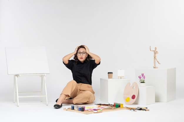 Вид спереди молодая женщина, сидящая внутри комнаты с мольбертом и красками, удивлена на белом фоне