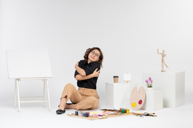 正面図白い背景の上のイーゼルペイントとタッセルと部屋の中に座っている若い女性